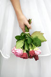 Bride. Hand of a bride, holding the bridal bouquet in front of her wedding dress down in a resigning, disappointed manner stock photography