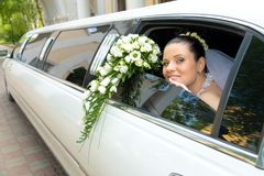 Bride. Image of beautiful bride showing her rose bouquet out of wedding limousine and looking at camera Stock Photo