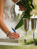 Bride. With wedding bunch of flowers (bouquet) signing marriage lines (certificate Royalty Free Stock Photo