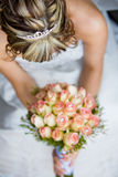 Bride from above. A vertical image of a caucasian bride holding her rose bouquet, photographed from above to show her hair Royalty Free Stock Images