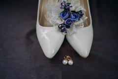 Bride accessories: lace blouse, garter, ballet flats, high-heeled shoes Stock Photos