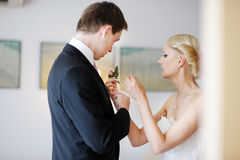 Bride adjusting groom's boutonniere Stock Photography