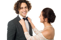 Bride adjusting her man's bow tie Stock Image