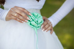 Bride adjusts flower on her dress Stock Photo