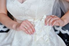 Bride adjusts white bow on her dress Royalty Free Stock Photo