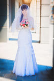 Bride against a blue modern building background Stock Image
