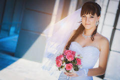 Bride against a blue modern building background Royalty Free Stock Photos