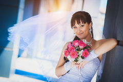 Bride against a blue modern building background Royalty Free Stock Images