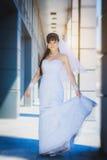 Bride against a blue modern building background. Happy bride in white dress against a blue modern building background Stock Image
