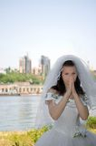 The bride against a city. The bride against the river and a city, looks in the cam and nervous royalty free stock photos