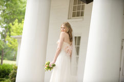 Bride against a columned porch Stock Image