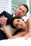 Bride And Groom Lying In Bedroom With Orchids Royalty Free Stock Images