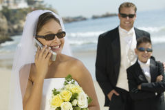 Bride Answering Mobilephone At Beach. Happy bride answering mobilephone with groom and ring bearer in background at beach Stock Images