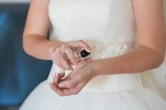 Bride applying perfume Royalty Free Stock Photos