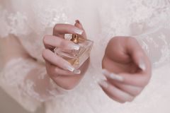 Bride applying perfume on her wrist Stock Images