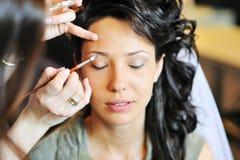 Bride applying wedding make-up by make-up artist Stock Photos