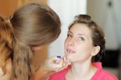 Bride applying wedding make-up by make-up artist (focus on brush) Stock Photography
