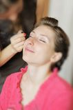 Bride applying wedding make-up by professional make-up artist Royalty Free Stock Images