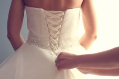 bride from the back, geting wedding dress tied Royalty Free Stock Photography