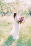 The bride with the back tattoo is the long white dress is turning around to look at the pink bouquet of the flowers. Composition of the spring field royalty free stock photography