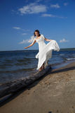 Bride balancing on trunk Royalty Free Stock Images