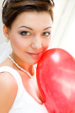 Bride with balloon. Young bride looks into camera holding red balloon royalty free stock images