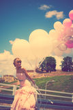 Bride with balloons. Happy bride in elegant wedding-dress hold balloons outdoor summer day, retro colors, Belgrade fortress in the background stock photography