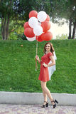 Bride with balloons standing in the park Royalty Free Stock Photos