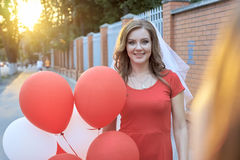 Bride with balloons standing in the park Stock Photos