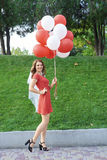 Bride with balloons standing in the park Royalty Free Stock Images