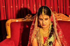 Bride in Bangladesh. Dhaka, Bangladesh - circa July 2012: Young black-haired bride in beautiful red and gold glittering dress sits on red couch and looks right royalty free stock image