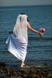 Bride barefoot in water. Back view of a bride walking barefoot into the waters of the ocean, holding her dress with her left hand, and a small bouquet of pink royalty free stock photography