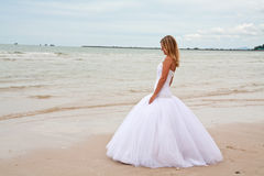 Bride on a beach. Beautiful and thoughtful young bride on a beach Royalty Free Stock Image