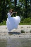 Bride on a beach. Bride jumping on a sandy beach Stock Photography