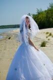 Bride on a beach. Bride on a sandy beach turns round itself Stock Photos