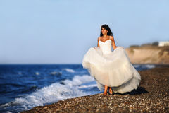 Bride on a beach in Santorini. A shot taken in a beach in Santorini of a lonely bride walking on the shore Royalty Free Stock Photography