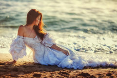 Bride on the beach. Young bride walking along the seashore in a white dress Stock Image