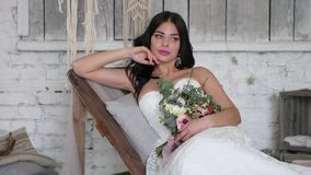 Bride is a beautiful brunette, lies on a couch in a beautiful interior in the style of a boho.  stock video footage