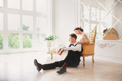 Bride in beautiful dress and groom in black suit sitting on sofa indoors in white studio interior like at home. Trendy wedding sty Royalty Free Stock Photography