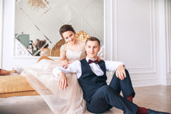Bride in beautiful dress and groom in black suit sitting on sofa indoors in white studio interior like at home. Trendy wedding sty royalty free stock images