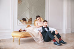 Bride in beautiful dress and groom in black suit sitting on sofa indoors in white studio interior like at home. Trendy wedding sty royalty free stock photo