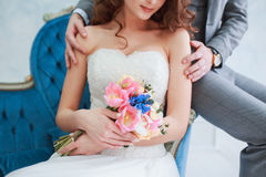 Bride in beautiful dress and groom in gray suit sitting on sofa indoors in white studio interior like at home. Stock Image