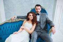 Bride in beautiful dress and groom in gray suit sitting on sofa indoors in white studio interior like at home. Royalty Free Stock Photos