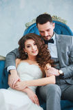 Bride in beautiful dress and groom in gray suit sitting on sofa indoors in white studio interior like at home. Royalty Free Stock Images