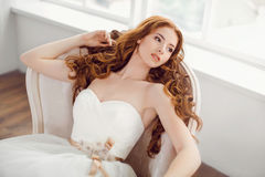 Bride in beautiful dress laying resting on sofa indoors. Bride in beautiful dress laying on sofa indoors in white studio interior like at home. Trendy wedding Royalty Free Stock Photography