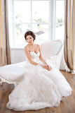 Bride in beautiful dress sitting on chair indoors. Bride in beautiful dress sitting on sofa indoors in white studio interior like at home. Trendy wedding style royalty free stock photography