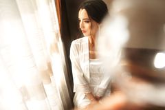 Bride in beautiful dress sitting on chair indoors in white studio interior like at home. Trendy wedding style shot stock images