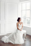 Bride in beautiful dress sitting on chair indoors. In white studio interior like at home. Trendy wedding style shot in full length. Young attractive multi stock photo