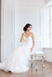 Bride in beautiful dress sitting on chair indoors. In white studio interior like at home. Trendy wedding style shot in full length. Young attractive multi stock photography