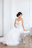 Bride in beautiful dress sitting on chair indoors. In white studio interior like at home. Trendy wedding style shot in full length. Young attractive multi stock images